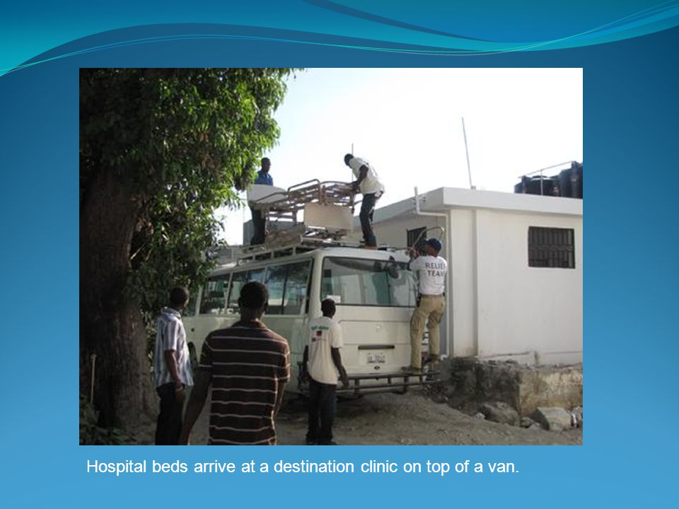 Hospital beds arrive at a destination clinic on top of a van.