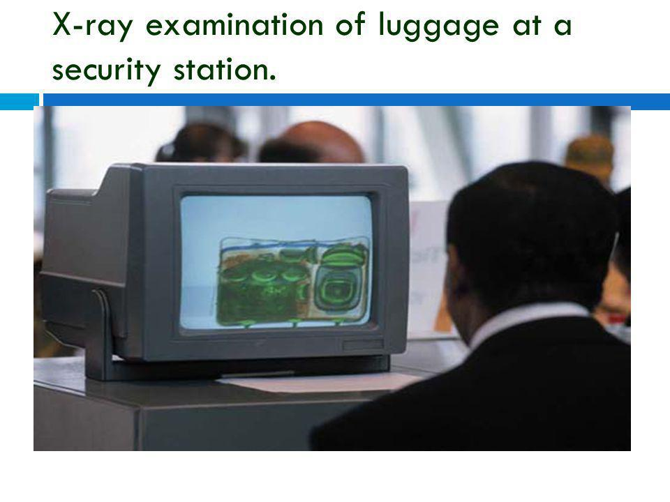 X-ray examination of luggage at a security station.