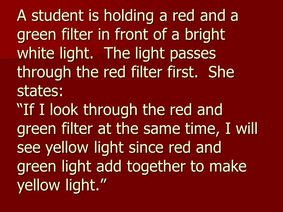 A student is holding a red and a green filter in front of a bright white light.