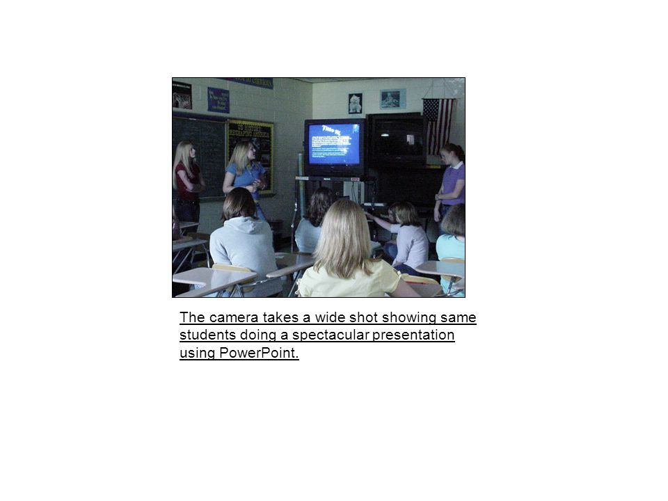 The camera takes a wide shot showing same students doing a spectacular presentation using PowerPoint.