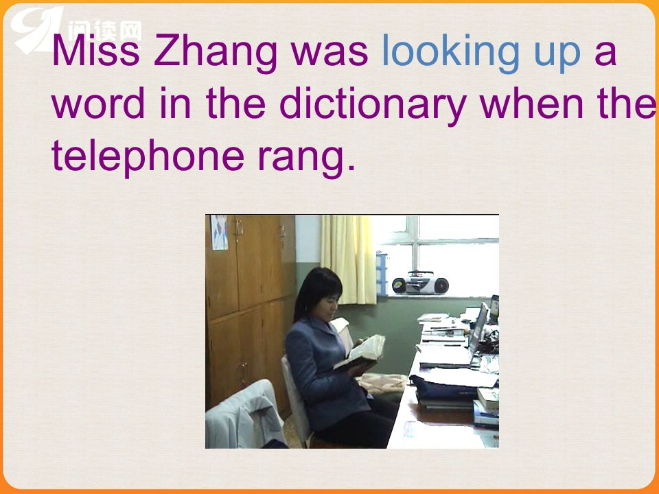 Miss Zhang was looking up a word in the dictionary when the telephone rang.