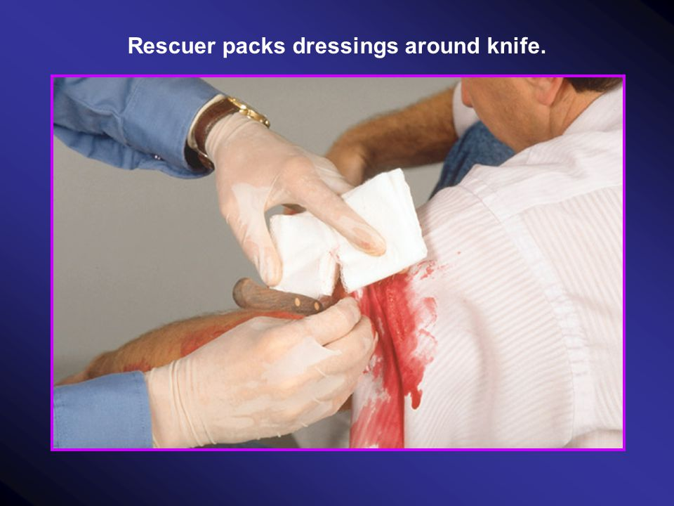 Rescuer packs dressings around knife.