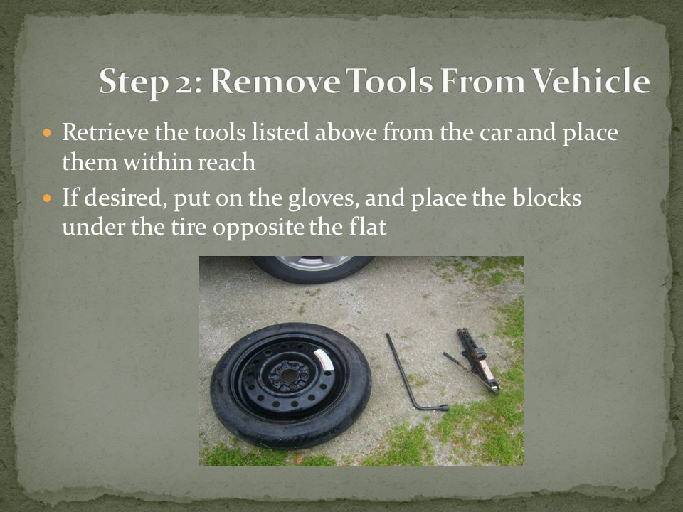 Retrieve the tools listed above from the car and place them within reach If desired, put on the gloves, and place the blocks under the tire opposite the flat