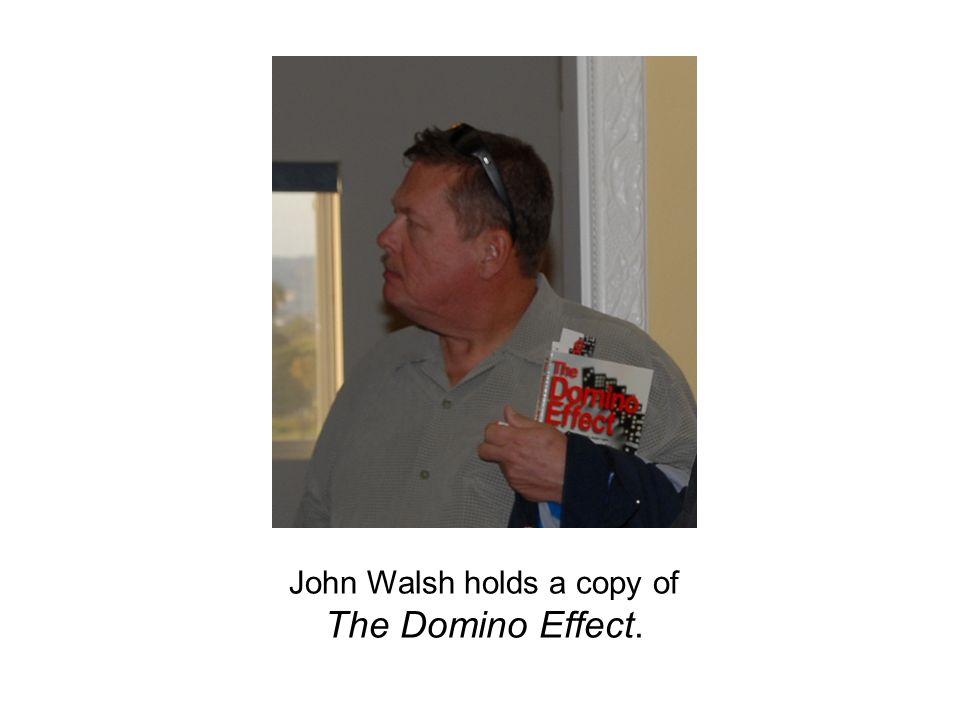 John Walsh holds a copy of The Domino Effect.