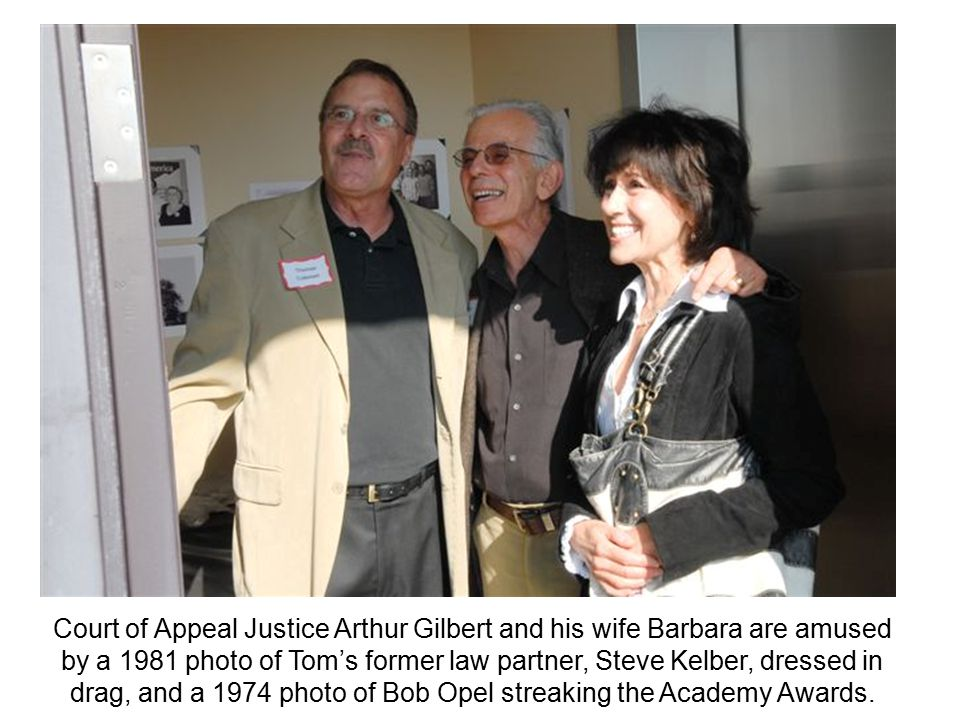 Court of Appeal Justice Arthur Gilbert and his wife Barbara are amused by a 1981 photo of Tom's former law partner, Steve Kelber, dressed in drag, and a 1974 photo of Bob Opel streaking the Academy Awards.