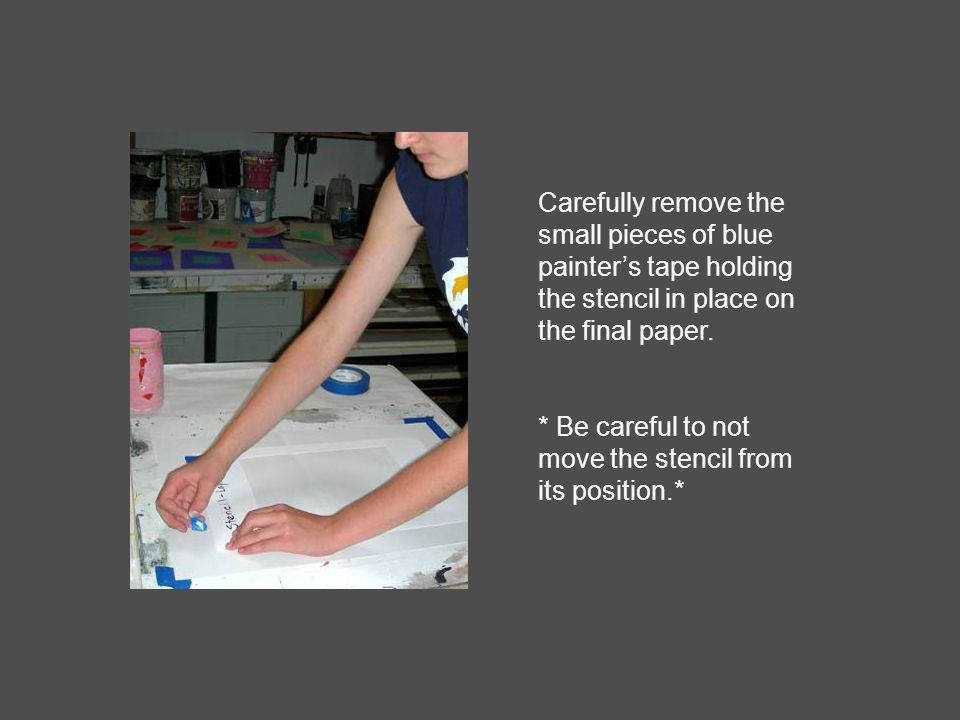 Carefully remove the small pieces of blue painter's tape holding the stencil in place on the final paper.