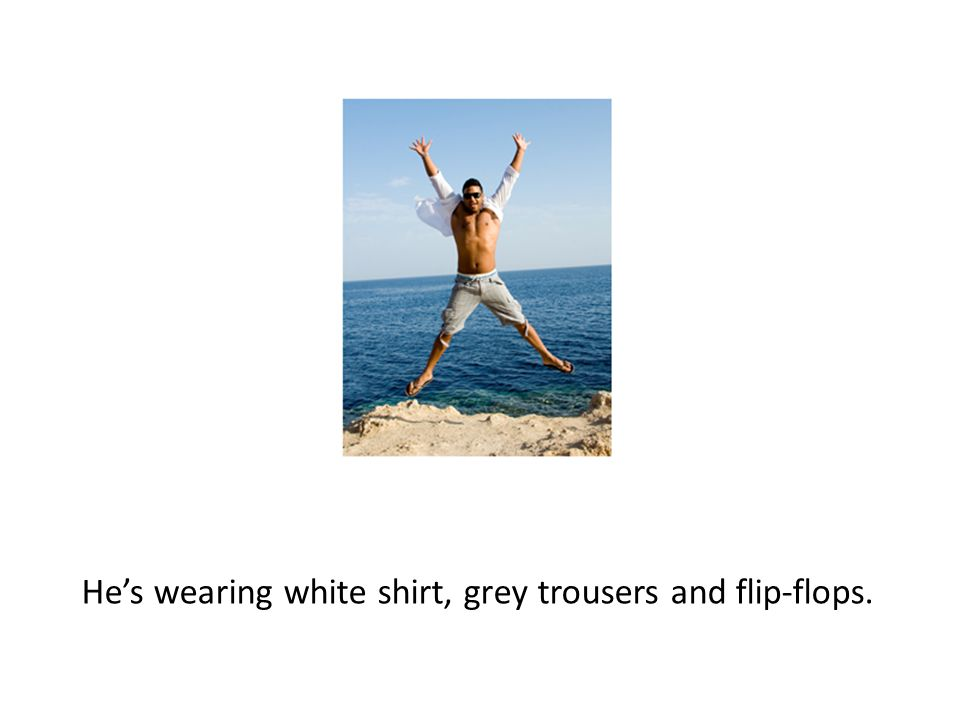 He's wearing white shirt, grey trousers and flip-flops.