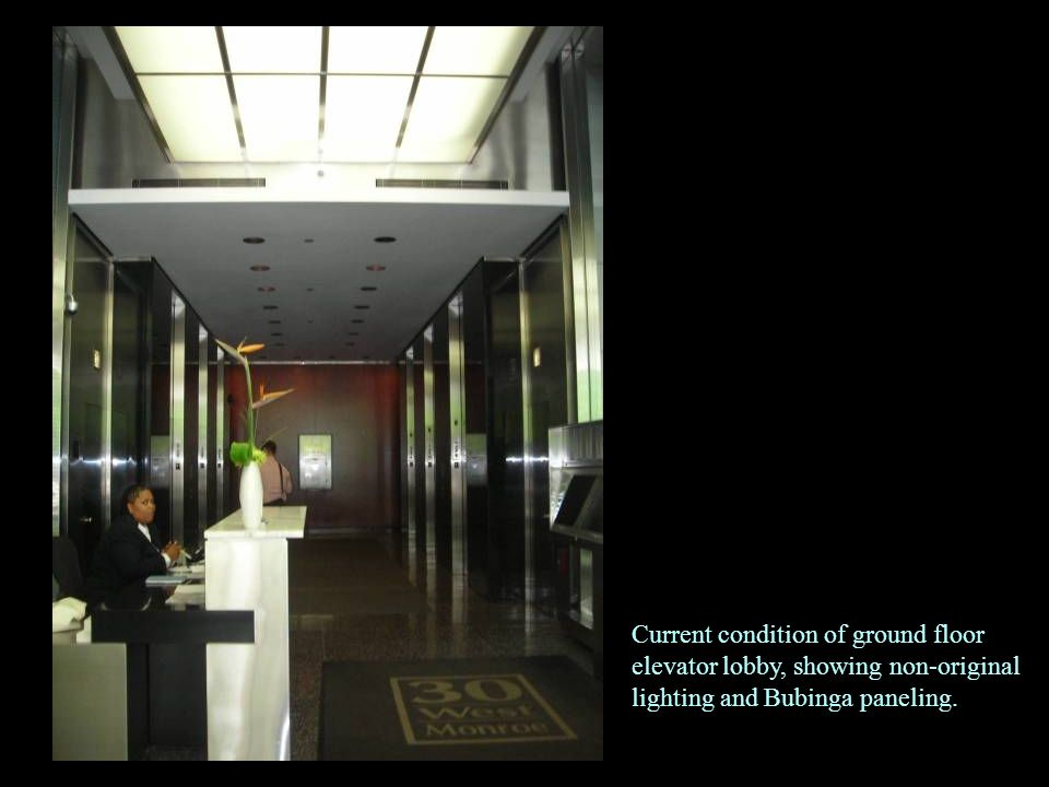 Current condition of ground floor elevator lobby, showing non-original lighting and Bubinga paneling.
