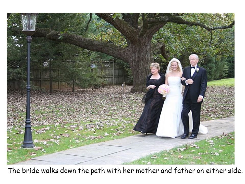The bride walks down the path with her mother and father on either side.