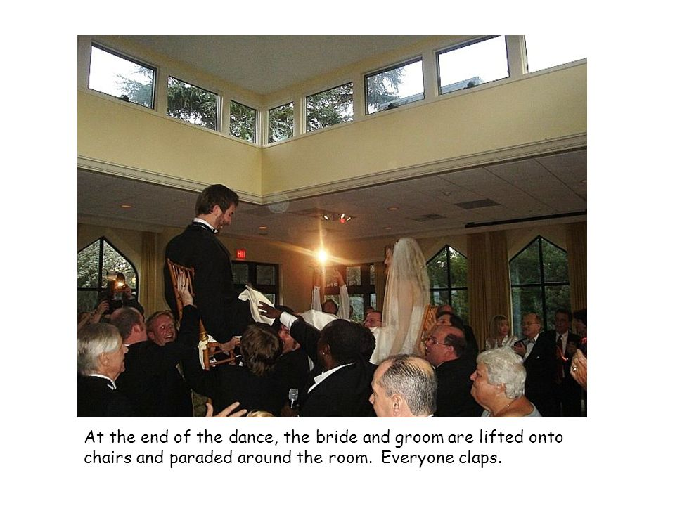 At the end of the dance, the bride and groom are lifted onto chairs and paraded around the room.