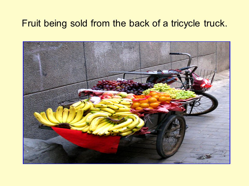 Fruit being sold from the back of a tricycle truck.