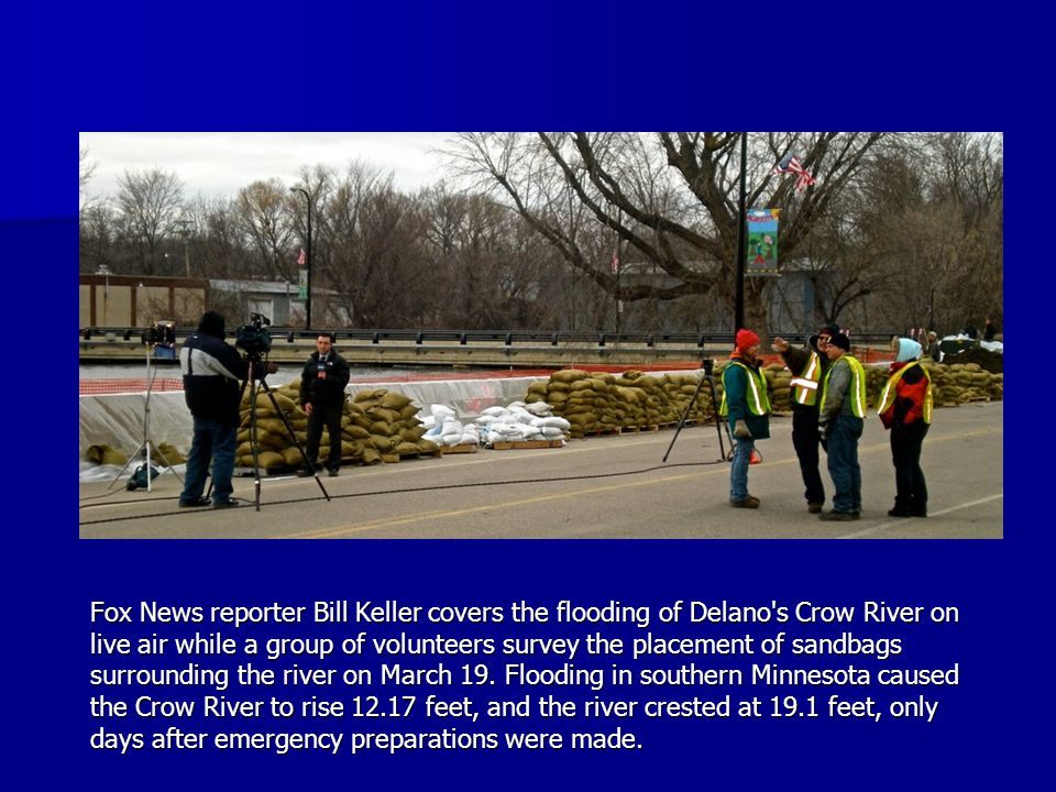 Fox News reporter Bill Keller covers the flooding of Delano s Crow River on live air while a group of volunteers survey the placement of sandbags surrounding the river on March 19.