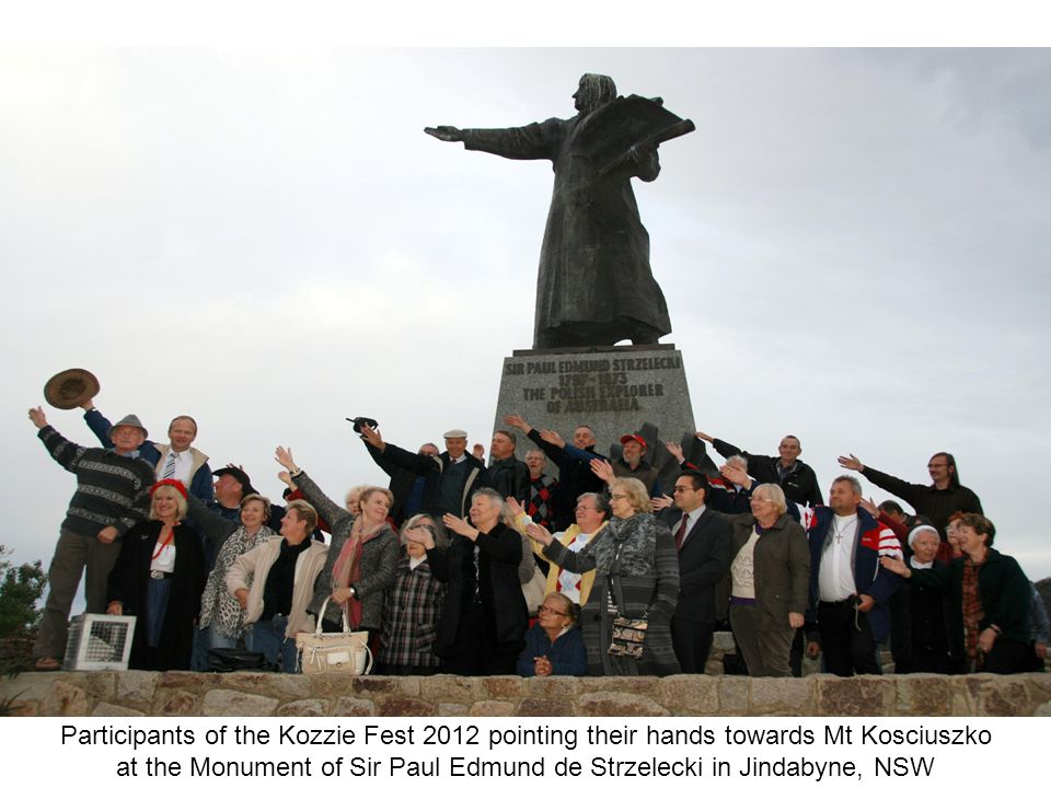 Participants of the Kozzie Fest 2012 pointing their hands towards Mt Kosciuszko at the Monument of Sir Paul Edmund de Strzelecki in Jindabyne, NSW