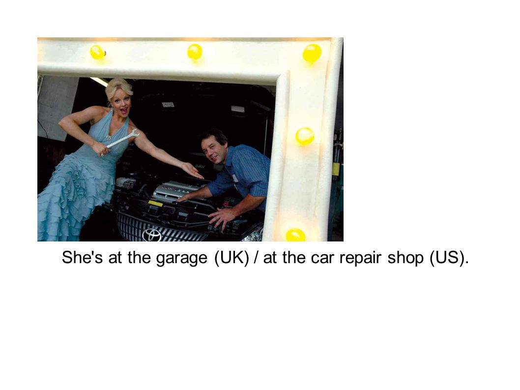 She s at the garage (UK) / at the car repair shop (US).