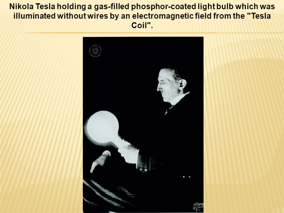 Nikola Tesla holding a gas-filled phosphor-coated light bulb which was illuminated without wires by an electromagnetic field from the Tesla Coil .