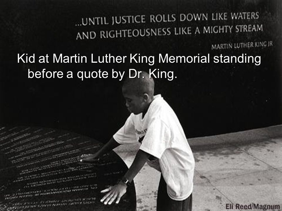 Kid at Martin Luther King Memorial standing before a quote by Dr. King.