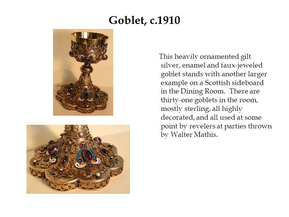 Goblet, c.1910 This heavily ornamented gilt silver, enamel and faux-jeweled goblet stands with another larger example on a Scottish sideboard in the Dining Room.