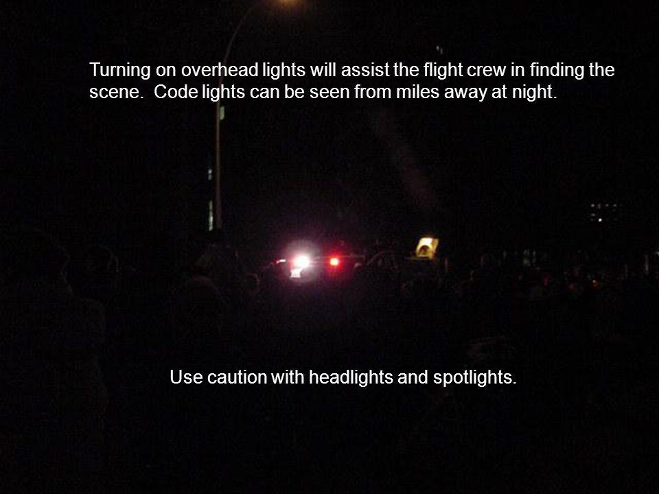 Turning on overhead lights will assist the flight crew in finding the scene.